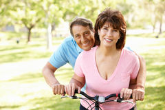 Hispanic senoir couple with bike smiling at camera. In field Royalty Free Stock Images