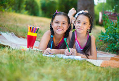 Hispanic sisters drawing in summer park Royalty Free Stock Photos