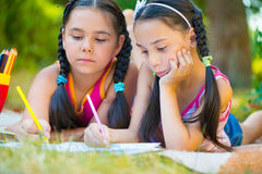 Hispanic sisters drawing in summer park Royalty Free Stock Images
