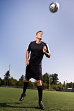 Hispanic soccer or football player heading a ball Royalty Free Stock Images