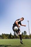 Hispanic soccer or football player kicking a ball. A shot of a hispanic soccer or football player kicking a ball stock images