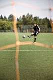 Hispanic soccer or football player kicking a ball Royalty Free Stock Image