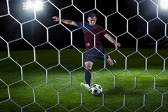Hispanic Soccer Player ready to shoot during a gam. E. View from behind the goal. Game played at night Stock Photos