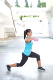 Hispanic sport woman doing lunges with two pink dumbbell, outdoor. Stock Photography