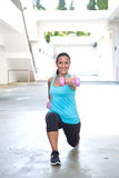 Hispanic sport woman doing lunges with two pink dumbbell, outdoor. Stock Photo