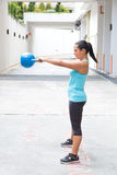 Hispanic sport woman swing the blue kettlebell, outdoor Royalty Free Stock Image