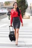 Hispanic stewardess crossing street with luggage bags. Portrait of hispanic stewardess crossing street with luggage bags Stock Image