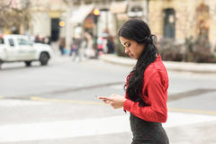 Hispanic stewardess in urban background looking at her mobile ph Stock Images