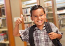 Hispanic Student Boy with Thumbs Up in the Library. Handsome Hispanic Student Boy with Back Pack and Thumbs Up in the Library Royalty Free Stock Images