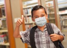 Free Hispanic Student Boy Wearing Face Mask With Thumbs Up And Backpack In The Library Stock Images - 189154884