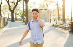 Hispanic student with curly hair walks on tree lined campus Stock Photos