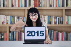 Hispanic student showing numbers 2015 on laptop Stock Images