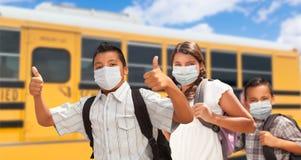 Three Hispanic Students Near School Bus Wearing Face Masks