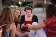 Hispanic Teen with Friends and Phone Royalty Free Stock Image