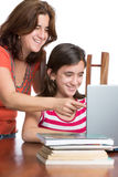 Hispanic teen and her mother browsing the web and laughing Royalty Free Stock Images