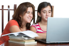 Hispanic teen and her mother working or browsing the web on a la Stock Photo