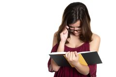 Hispanic teenage girl with glasses reading a book - On a white background stock photo