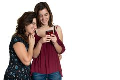 Hispanic teenage girl and her affectionate mother looking at a smartphone royalty free stock image