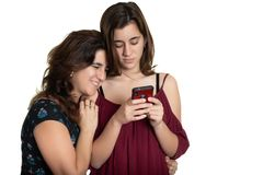 Hispanic teenage girl and her affectionate mother looking at a smartphone royalty free stock photo
