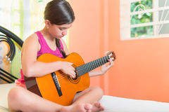 Hispanic teenage girl playing guitar at home Royalty Free Stock Images