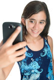 Hispanic teenage girl taking herself a photo with her mobile phone Royalty Free Stock Photo