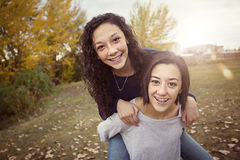 Hispanic Teenage girls having fun together outdoors. Cute hispanic teenage girls playing together outdoors during a warm fall day. Sun flare in the background Royalty Free Stock Photo