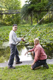 Hispanic teenager and father fishing in pond Royalty Free Stock Image