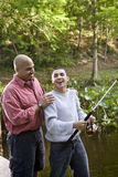 Hispanic teenager and father fishing in pond Stock Photos