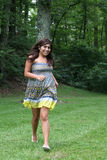 Hispanic teenager running. Attractive hispanic teenage girl running through the park wearing a dress Stock Photos