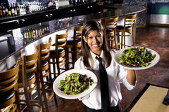 Hispanic waitress serving salads Royalty Free Stock Image