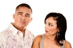 Hispanic wife looks suspiciously at her husband Stock Photos