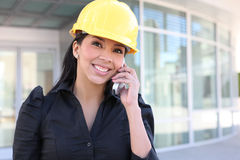 Hispanic Woman Architect on Phone. A young pretty hispanic woman architect with at building work site on phone Stock Photo