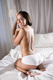 Hispanic woman in bed wearing underwear Stock Images