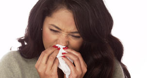 Hispanic woman blowing nose with tissue. And looking down Stock Photography