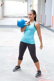 Hispanic woman in blue sports attire demonstrating the clean pose with a blue kettlebell, outdoor. Royalty Free Stock Image