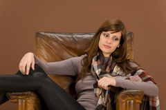 Hispanic woman on brown leather armchair Royalty Free Stock Image