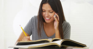Hispanic woman calling friend for help with homework. Woman calling friend for help with homework Royalty Free Stock Image