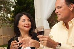 Hispanic Woman and Caucasian Man Enjoying Wine Stock Image