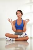 Hispanic woman closing eyes in yoga class Royalty Free Stock Image