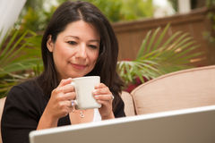 Hispanic Woman with Coffee and Laptop Stock Images