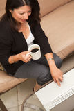 Hispanic Woman with Coffee and Laptop Royalty Free Stock Images