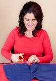 Hispanic woman cutting a piece of fabric Stock Photos