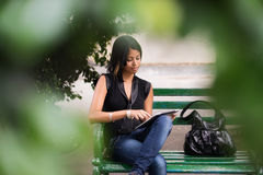 Hispanic woman with digital tablet pc on bench Stock Image