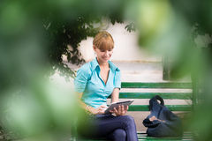 Hispanic woman with digital tablet pc on bench Royalty Free Stock Photos