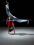 Hispanic woman doing capoeira martial art. Young adult latin american female handstanding and doing capoeira kick in gym, with streaks of led lights on waist Royalty Free Stock Image