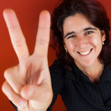 Hispanic woman doing the victory sign. Happy hispanic woman in her thirties doing the victory sign with her fingers on a bright red background Stock Photo