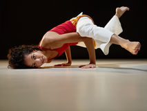 Hispanic woman doing yoga exercise. Portrait of young adult latin american female doing yoga and capoeira in gym. Horizontal shape, full length, side view, copy Royalty Free Stock Photo