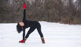 Hispanic woman doing yoga positions  outside in winter Stock Photos