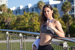 Hispanic woman drinking water during a workout session. Hispanic girl drinks water during a fitness session Royalty Free Stock Photography