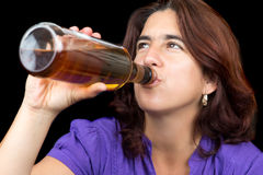 Hispanic woman drinking from a whisky or rum bottle Royalty Free Stock Photos